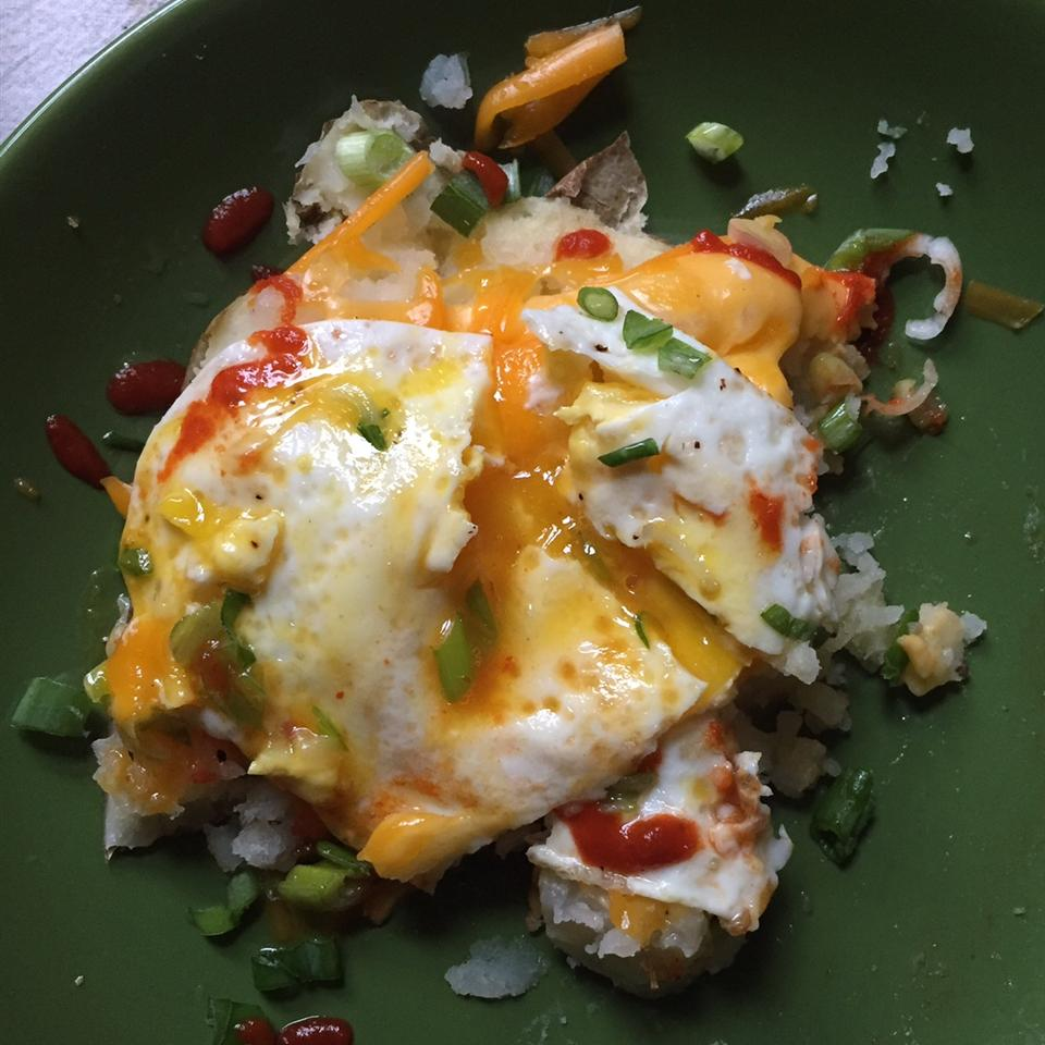 potato hash with fried egg on top with hot sauce