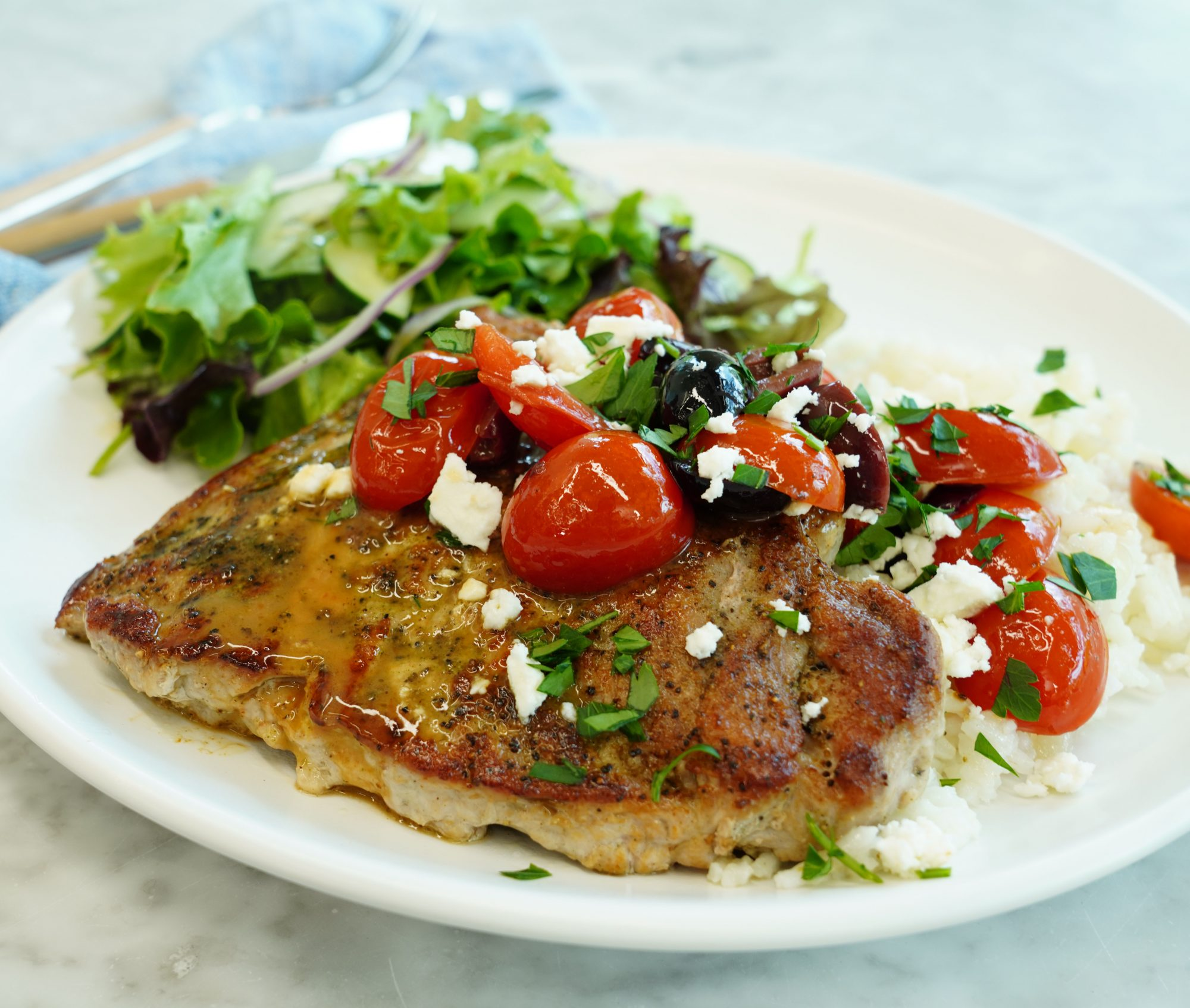 a browned pork chop topped with halved cherry tomatoes, crumbled feta, and kalamata olives on a plate with mixed greens in the background