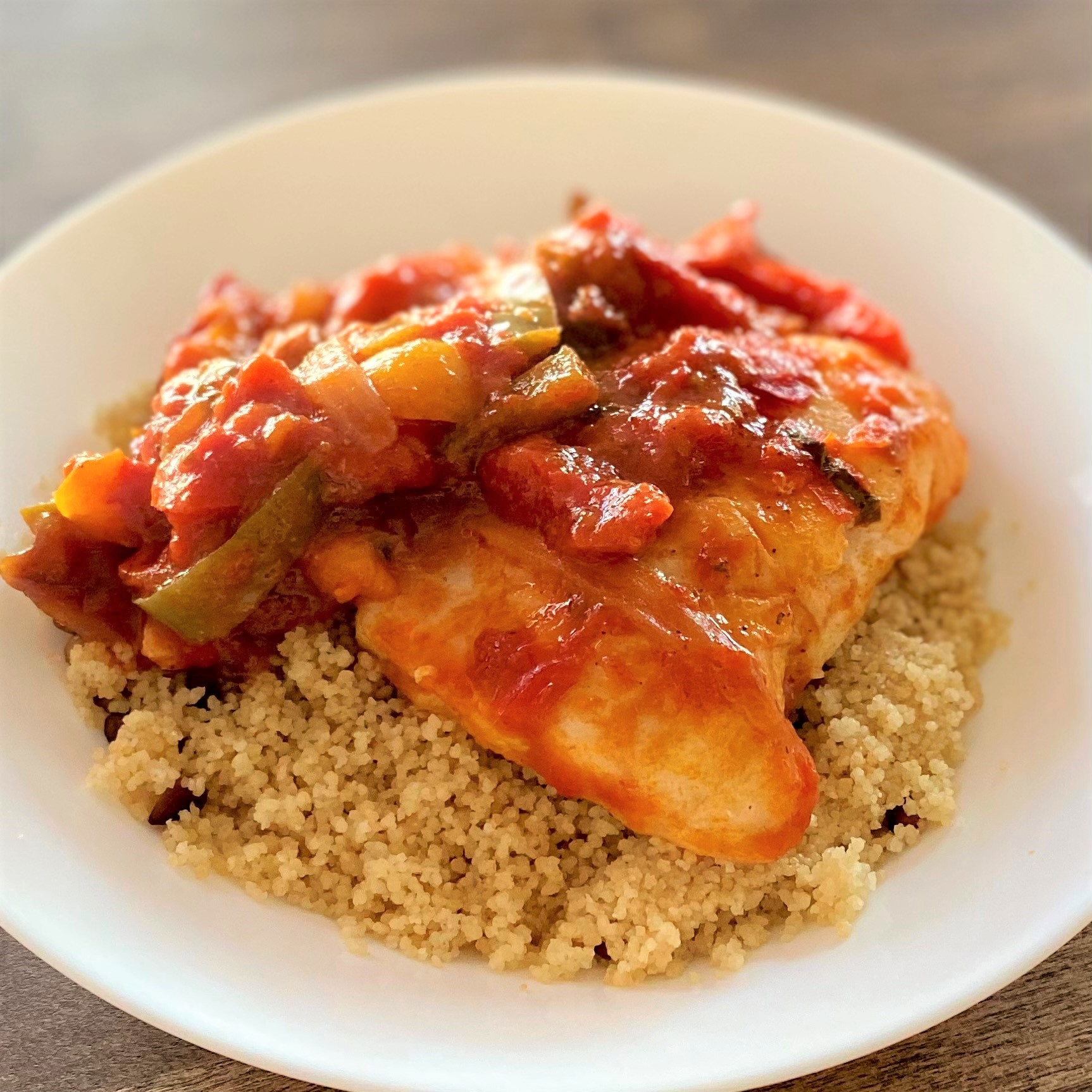 fish fillets in a tomato-based sauce served on a bed of couscous