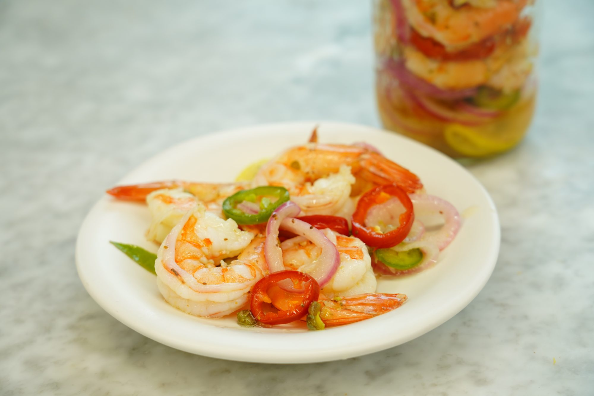 close up of best pickled shrimp on a plate with pickled peppers and onions
