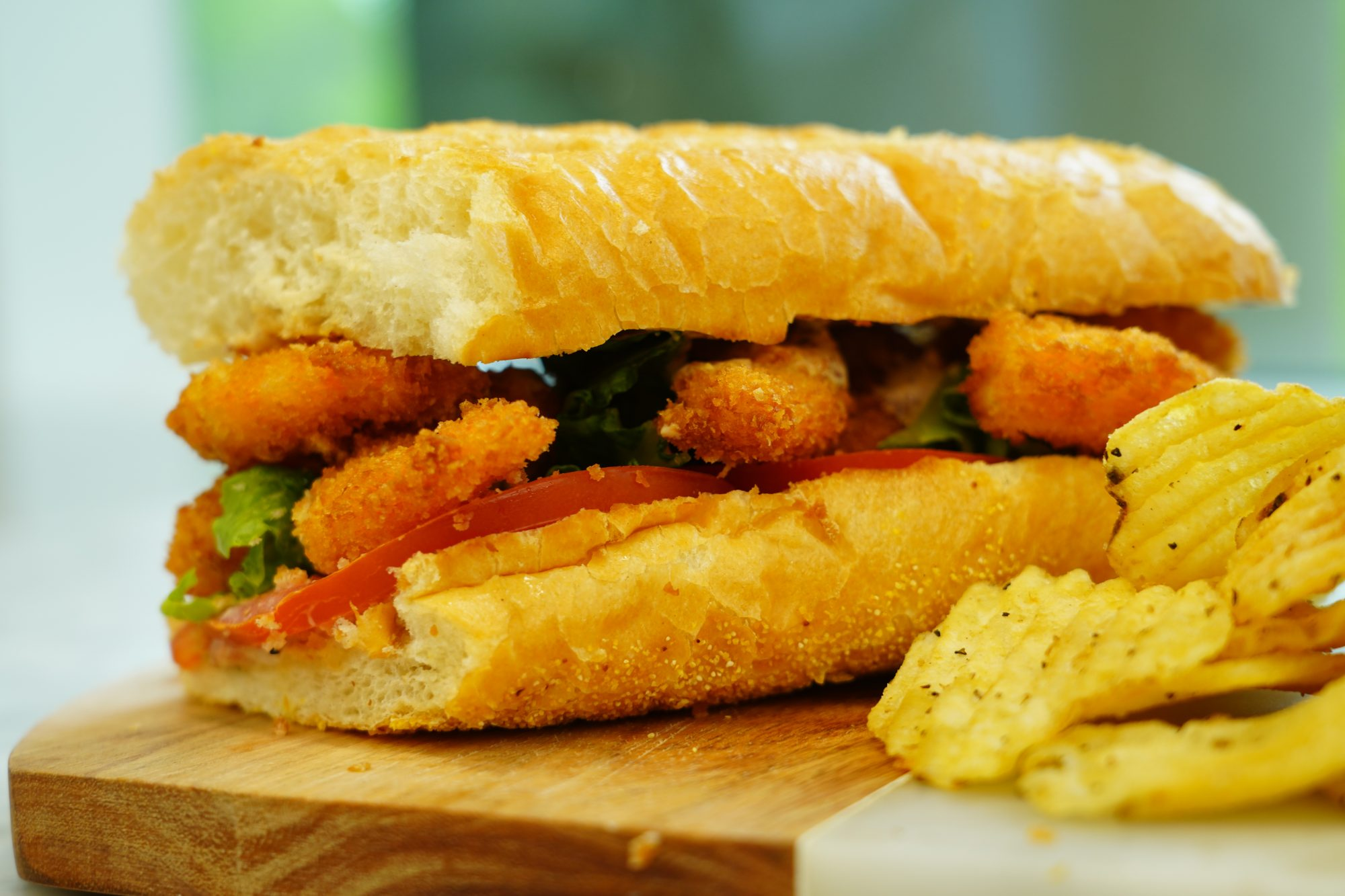 side view of a shrimp po' boy sandwich with fried shrimp, tomatoes, and lettuce on a french roll