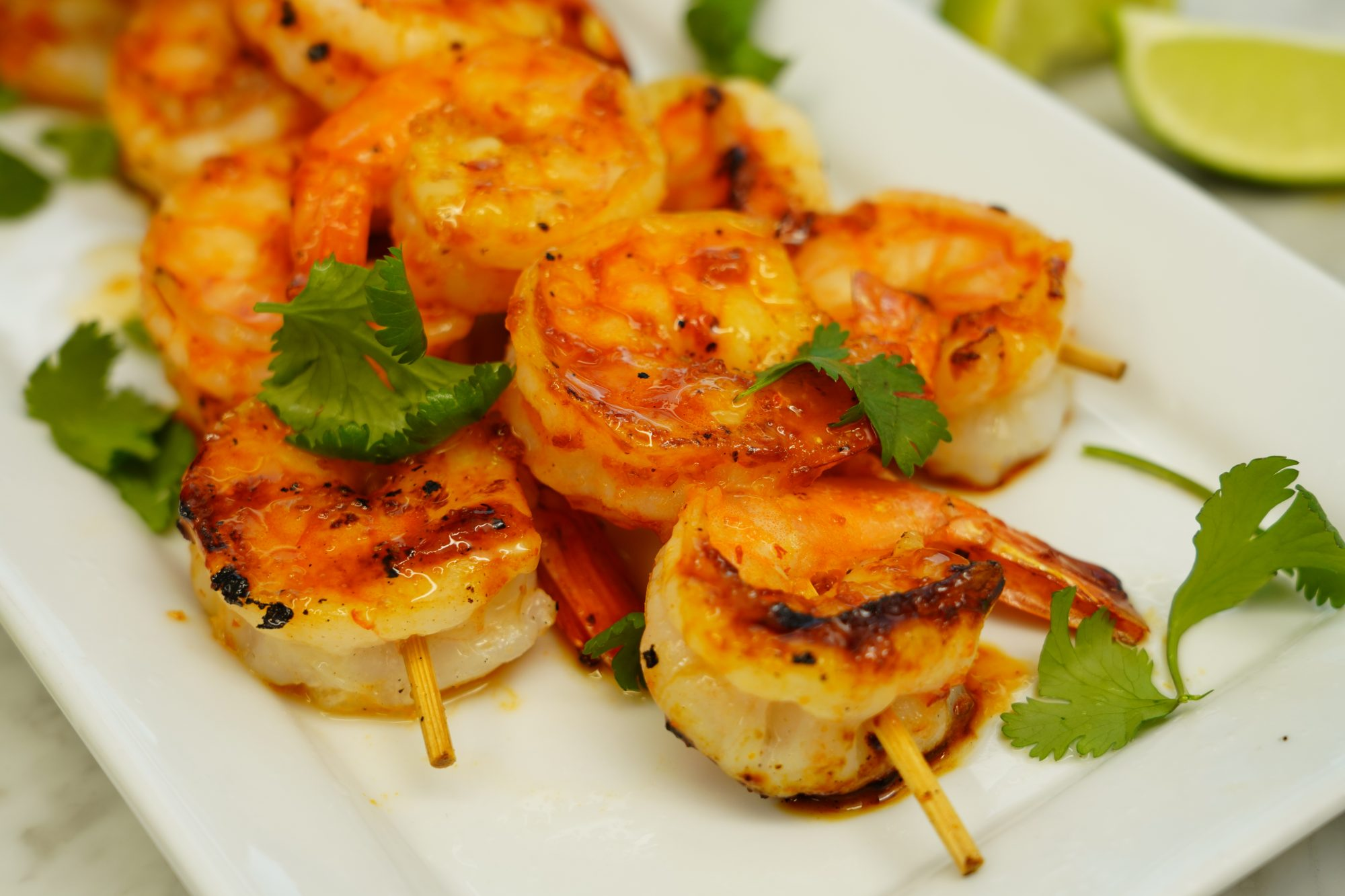 close up of sweet and spicy grilled shrimp threaded on skewers and served on a platter garnished with cilantro