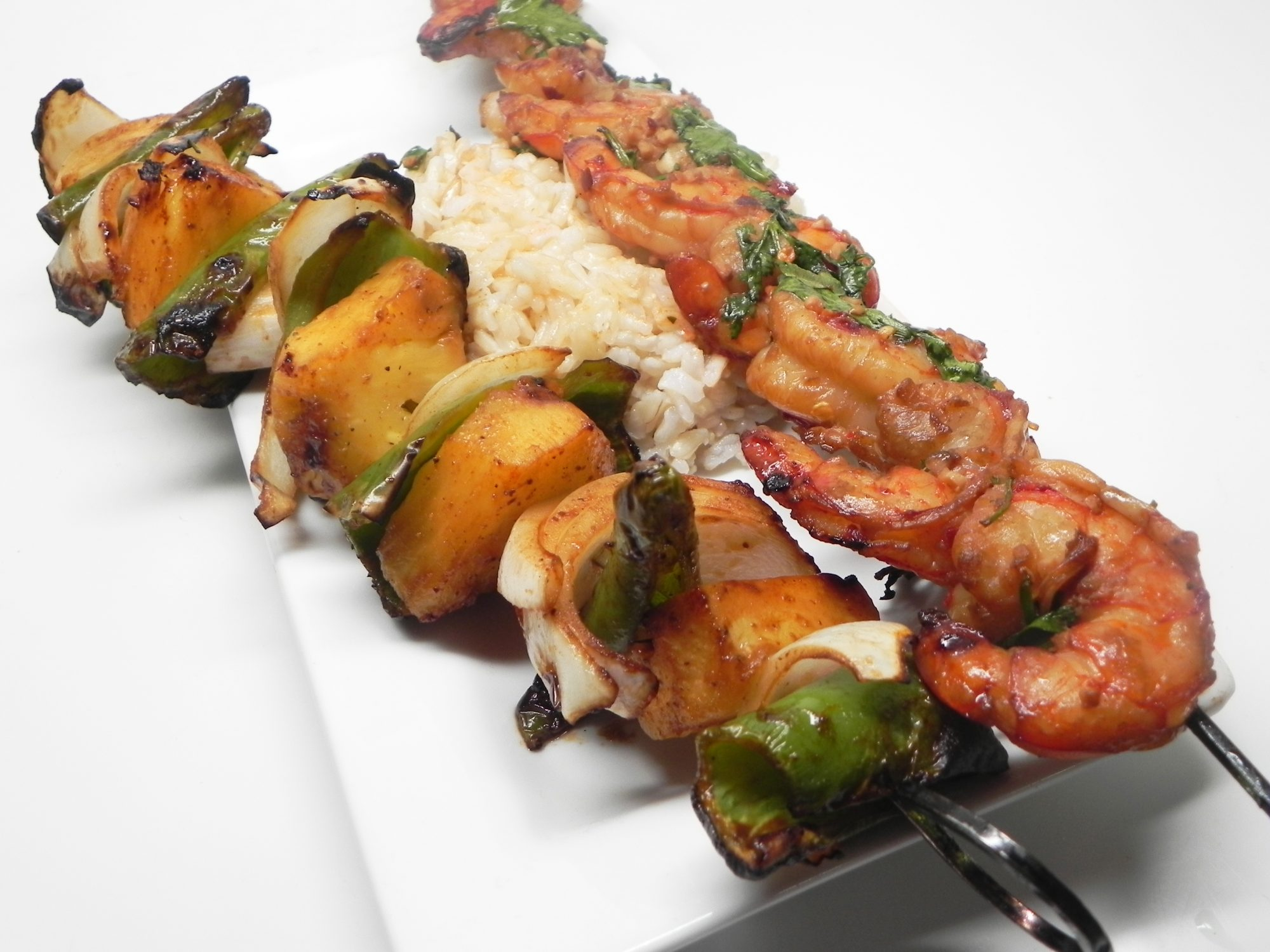 grilled shrimp, pineapple, onions, and peppers on skewers over rice