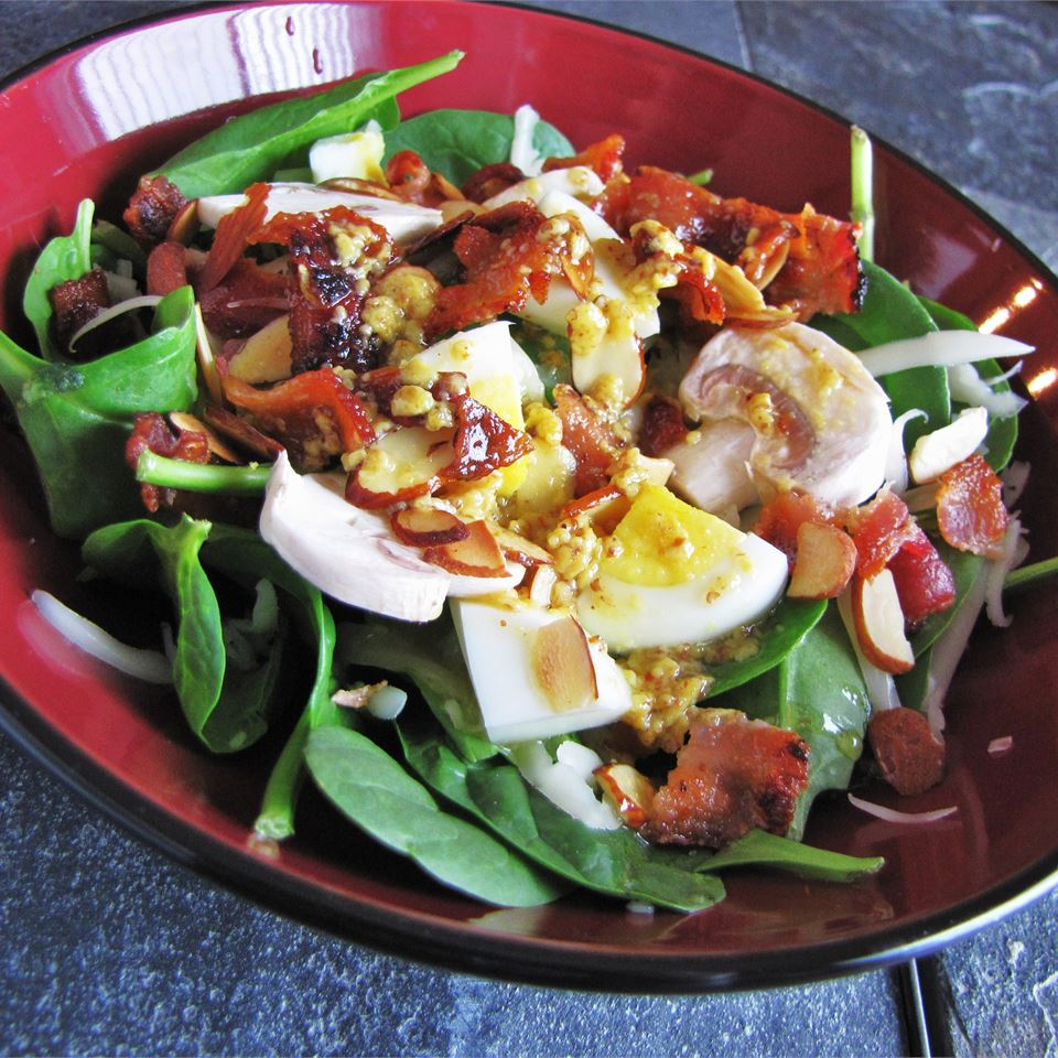 close up of spinach salad with bacon, eggs, nuts, mushrooms, onions, and warm mustard dressing