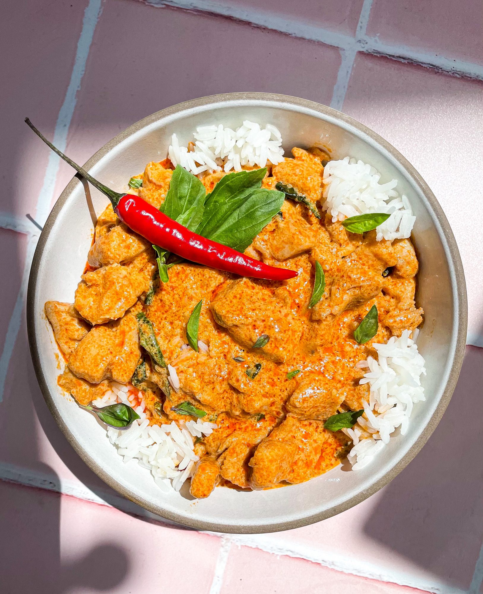 overhead shot red Thai curry with chili pepper garnish
