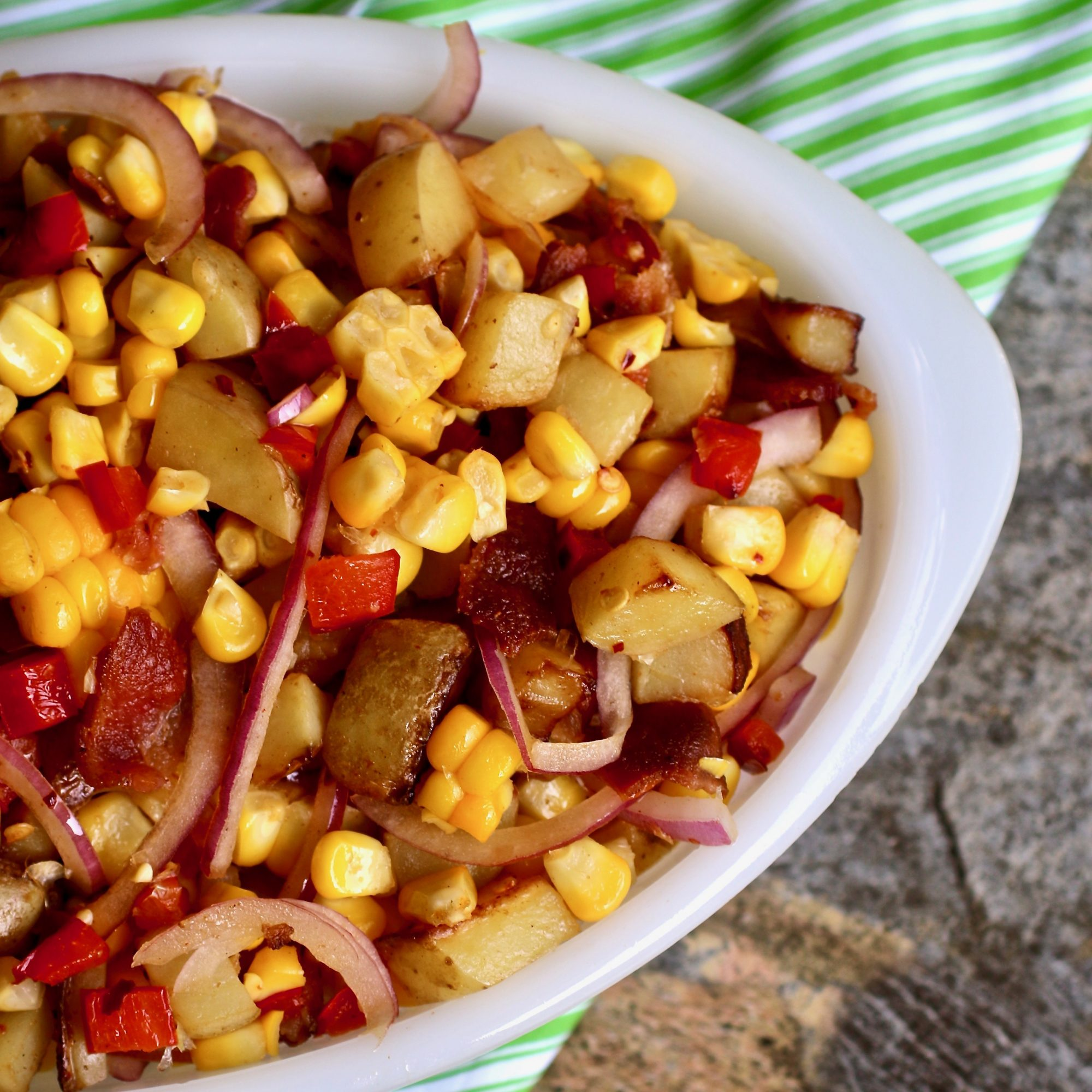 bowl of corn salad with bacon, red onion, potatoes, and peppers