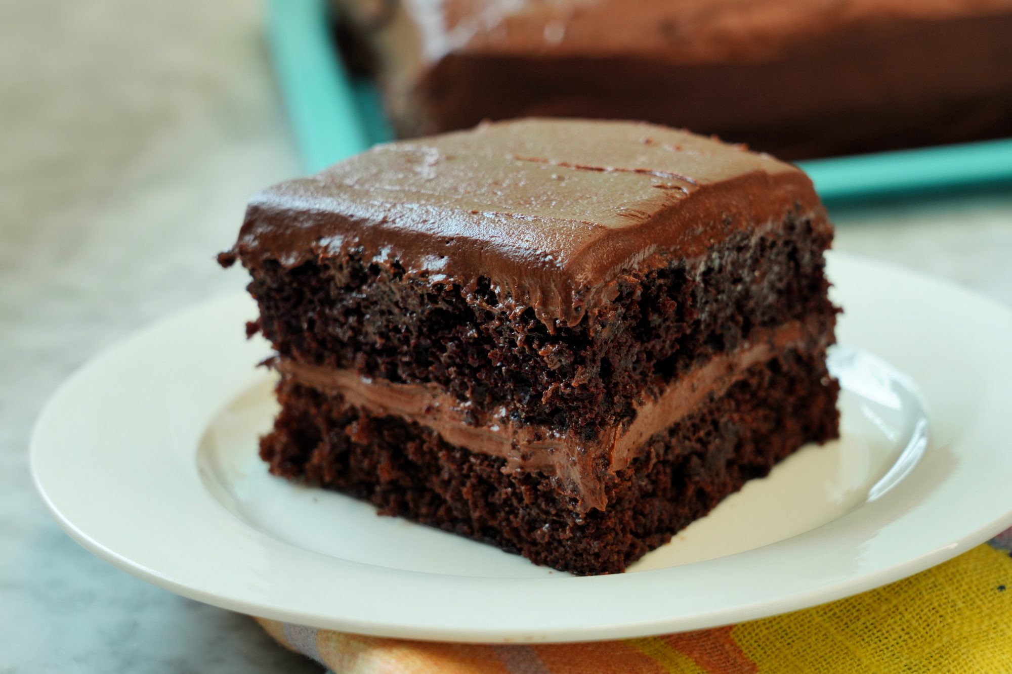 close up of a slice of One Bowl Chocolate Cake baked as a layered sheet cake with chocolate frosting