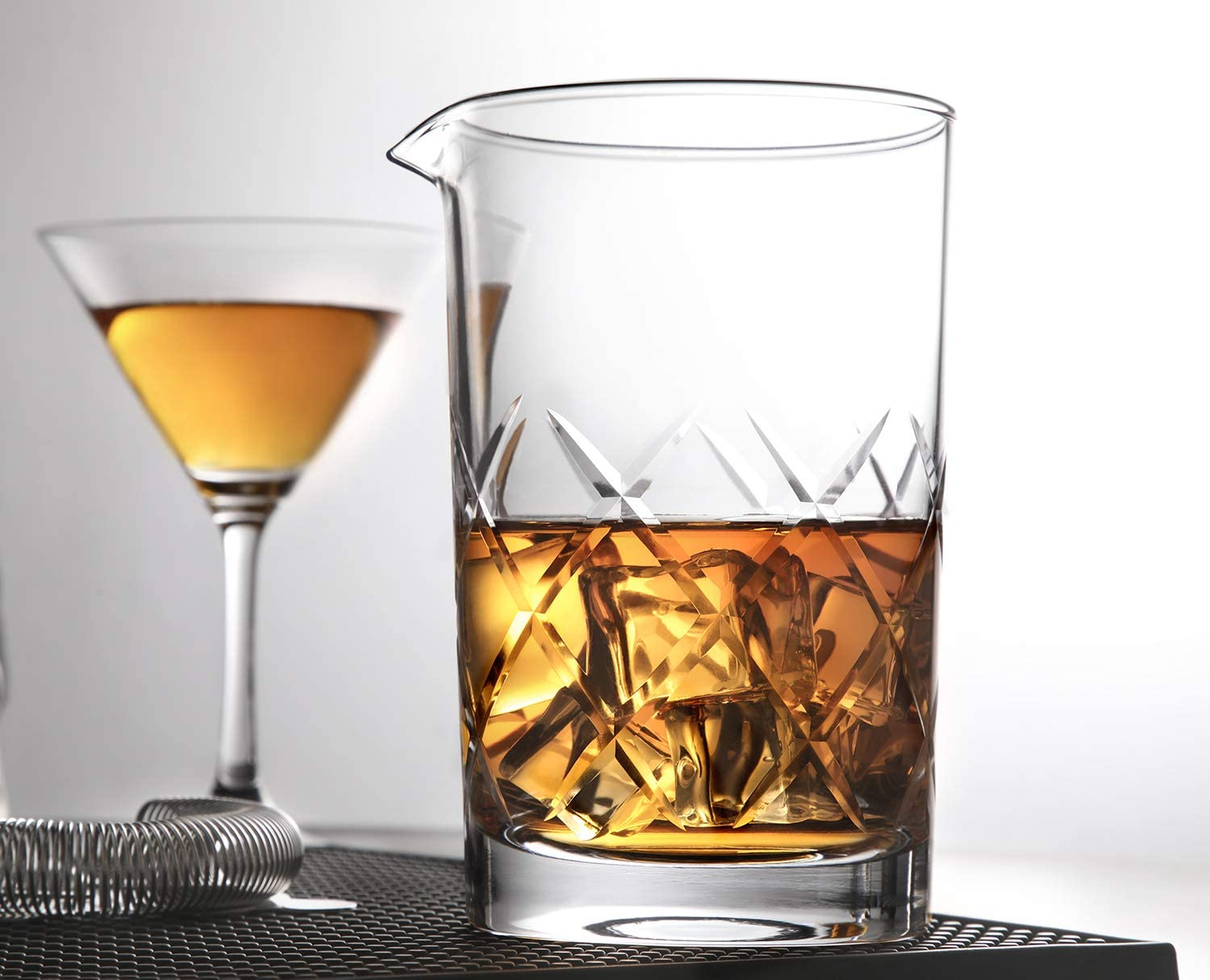 mixing glass with laser etching next to cocktail in martini glass