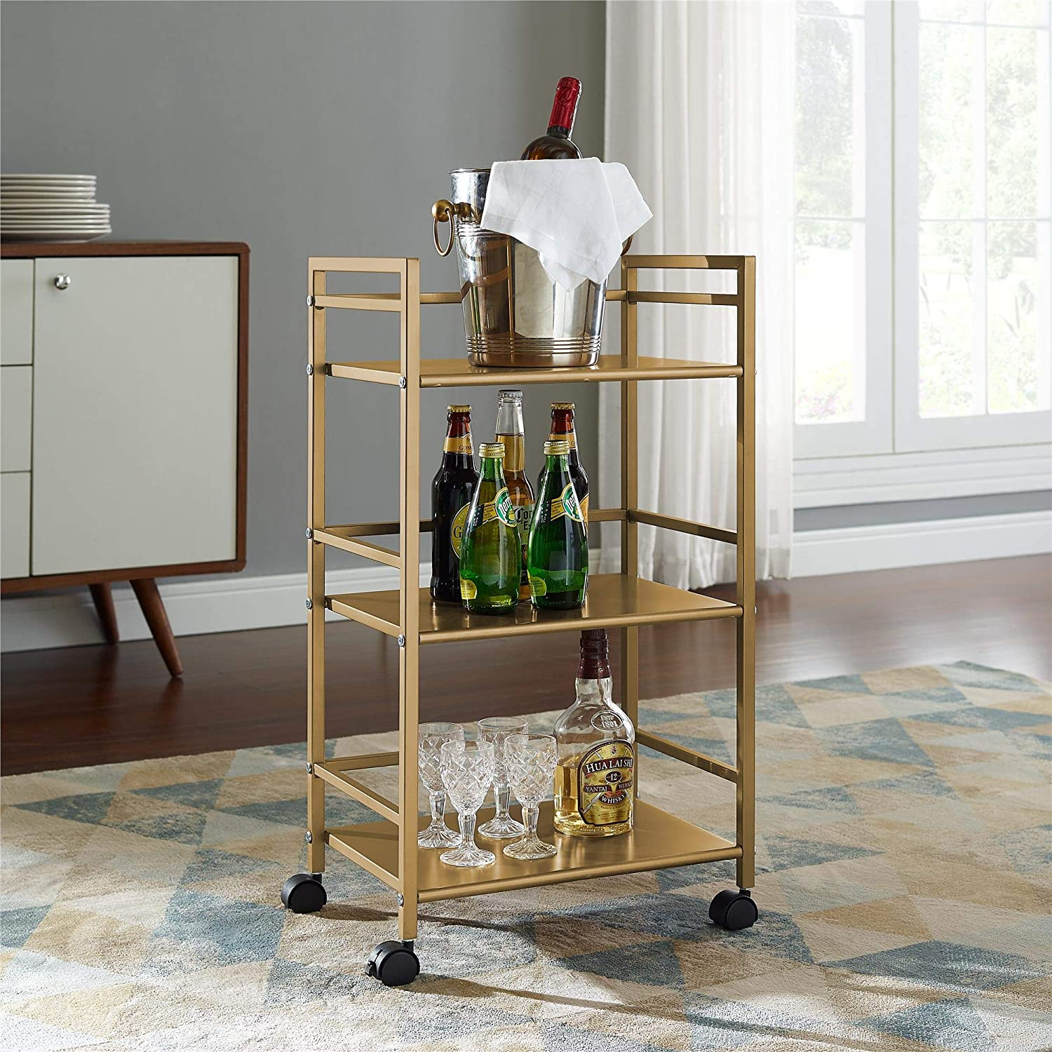 gold rolling bar cart with liquor and glasses on it