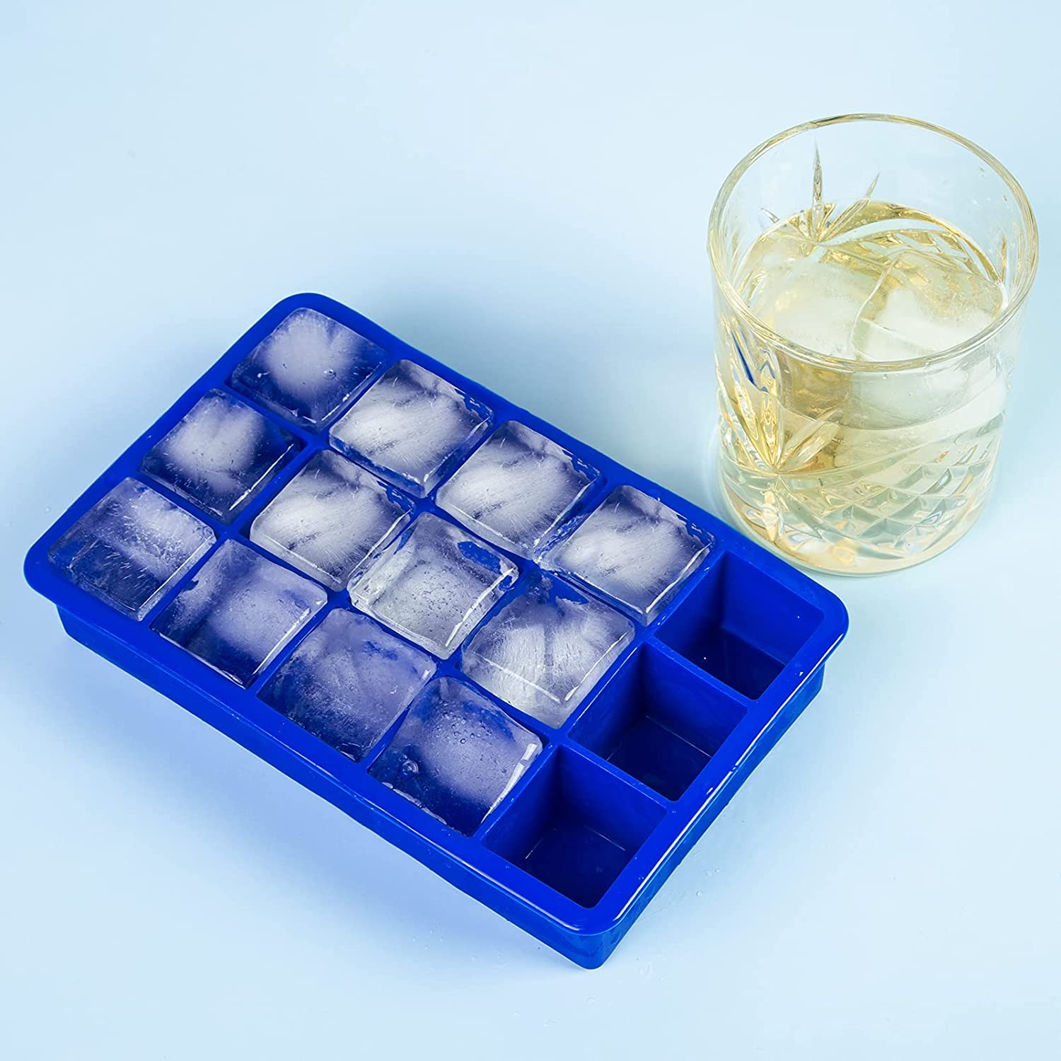 blue square ice cube mold next to cocktail in tumbler