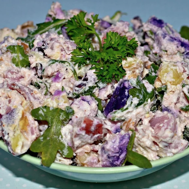 A container of low-fat yogurt and an ample amount of sour cream add creaminess and subtle tangy flavor to this warm potato salad. Arugula gives it a burst of healthy color.