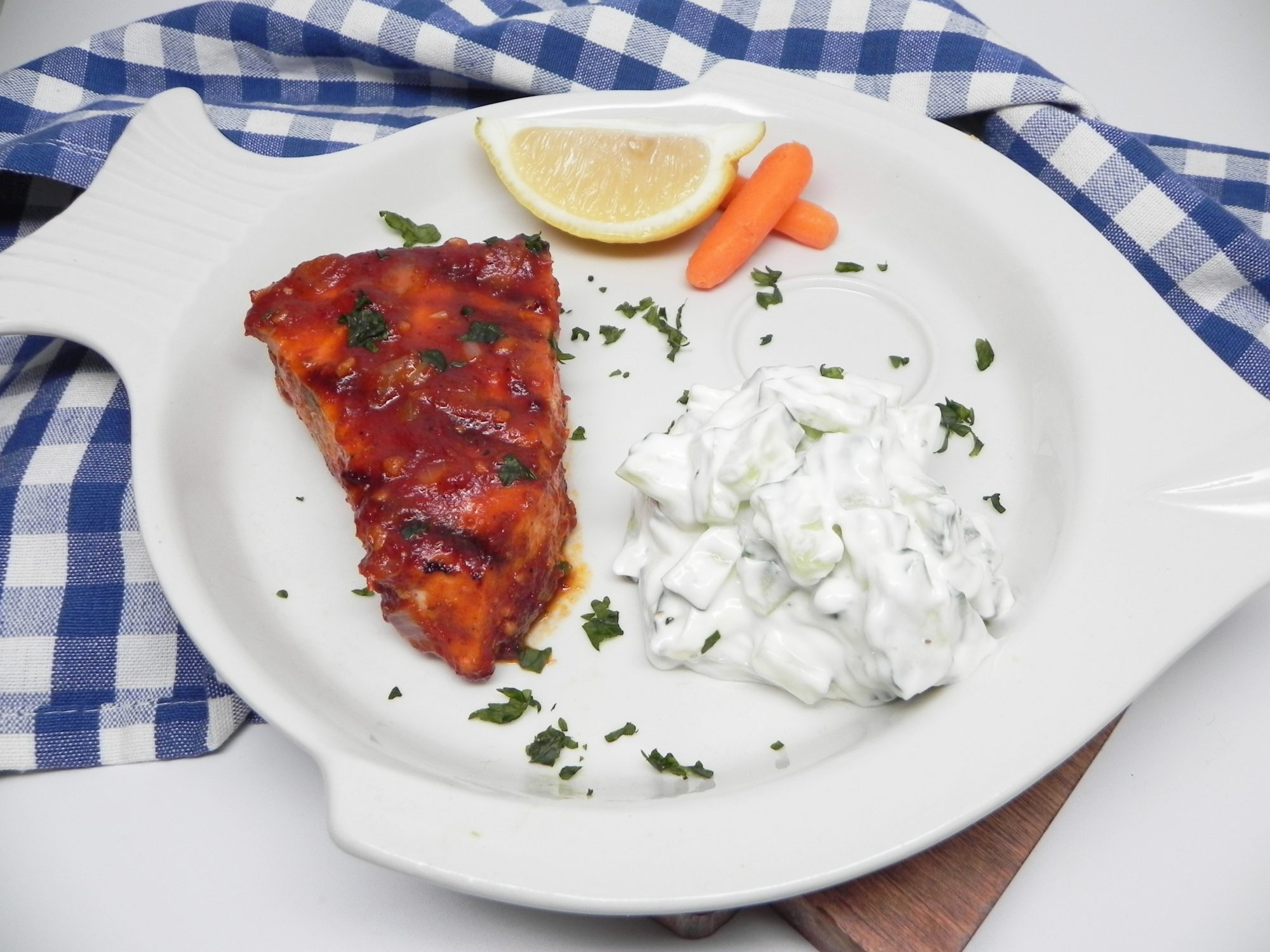 grilled swordfish with creamy cucumber sauce on white plate