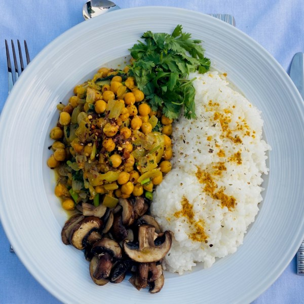 chickpea curry with rice and mushrooms on the side