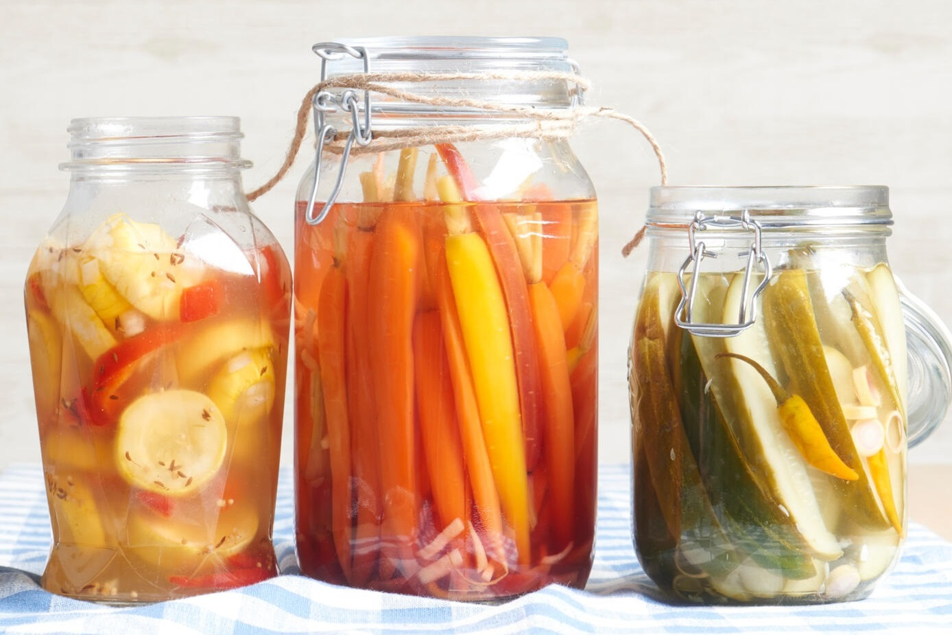 three glass jars full of pickled squash, carrots, and cucumbers