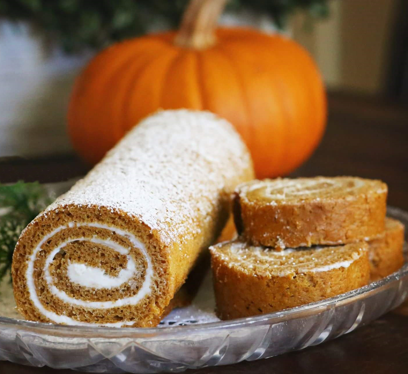 pumpkin roll with a few stacked sliced sit in front of a pumpkin