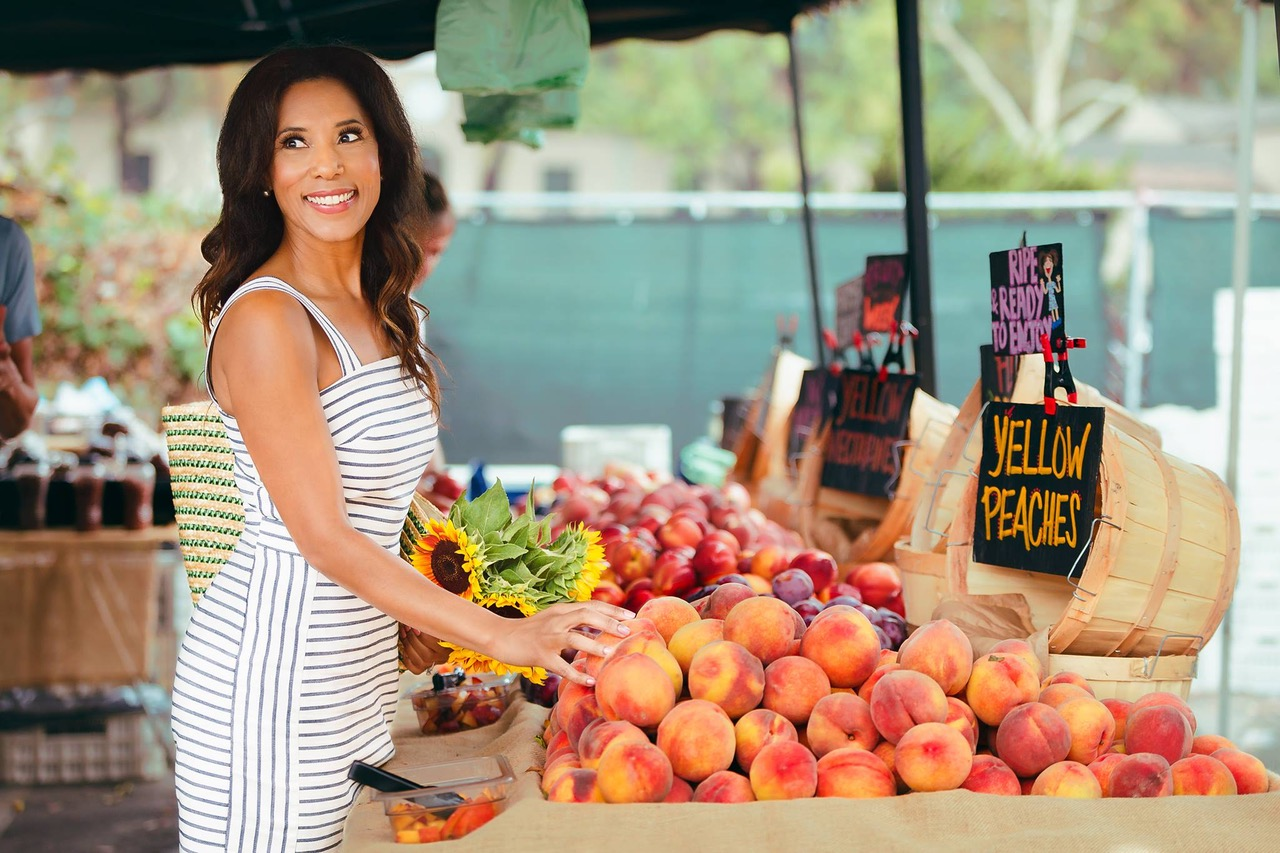 a woman stands at a fruit stand and looks over her right shoulder
