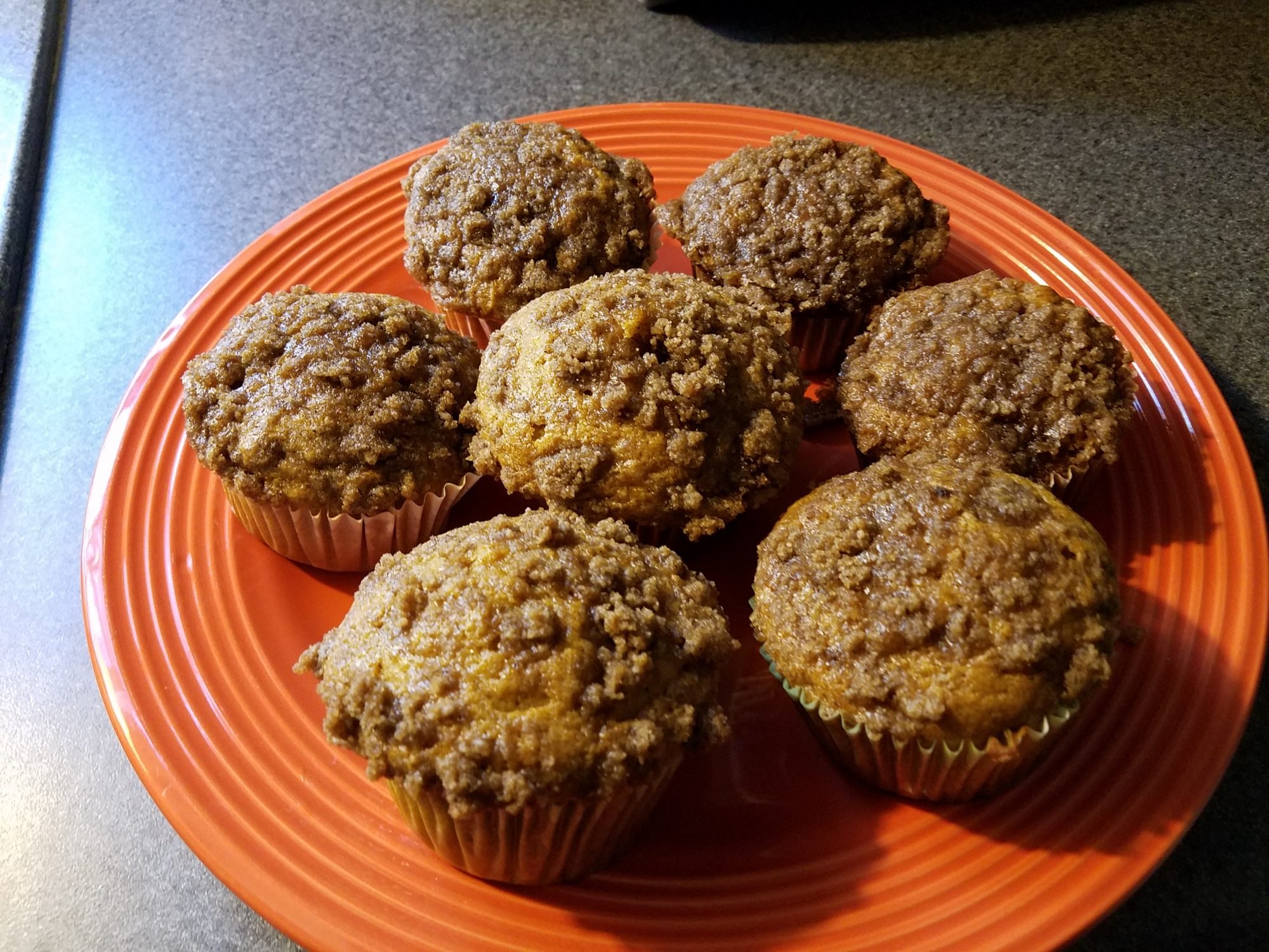 pumpkin muffins with streusel topping on orange plate