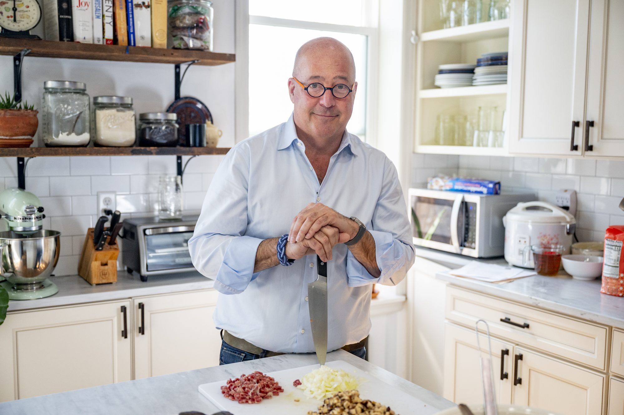 Andrew Zimmern at kitchen counter holding a knife