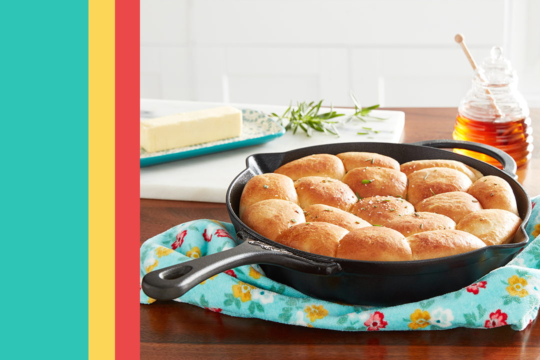 a cast iron pan with yeast rolls on a floral trivet