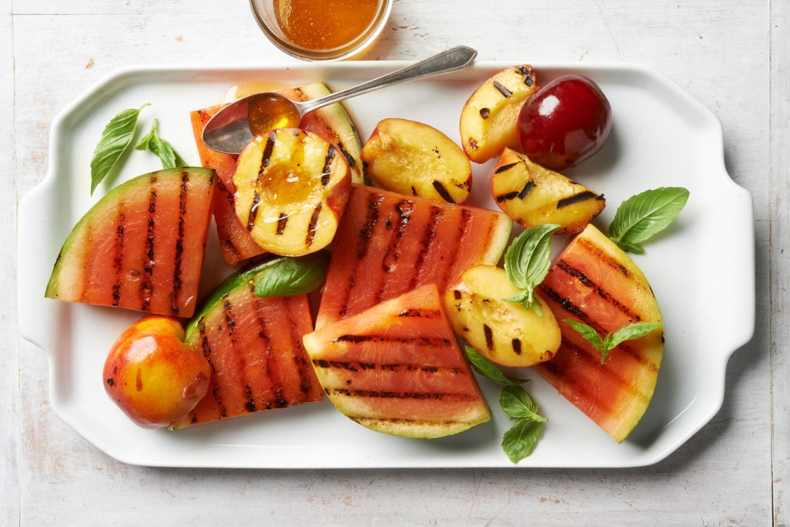 platter of grilled peaches and watermelon garnished with honey and fresh basil leaves