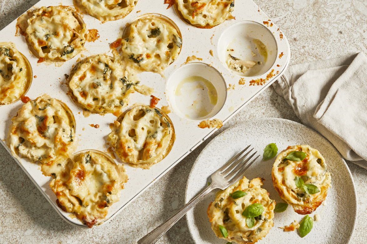 Muffin tin with chicken florentine alfredo lasagna cups with two removed and plated.