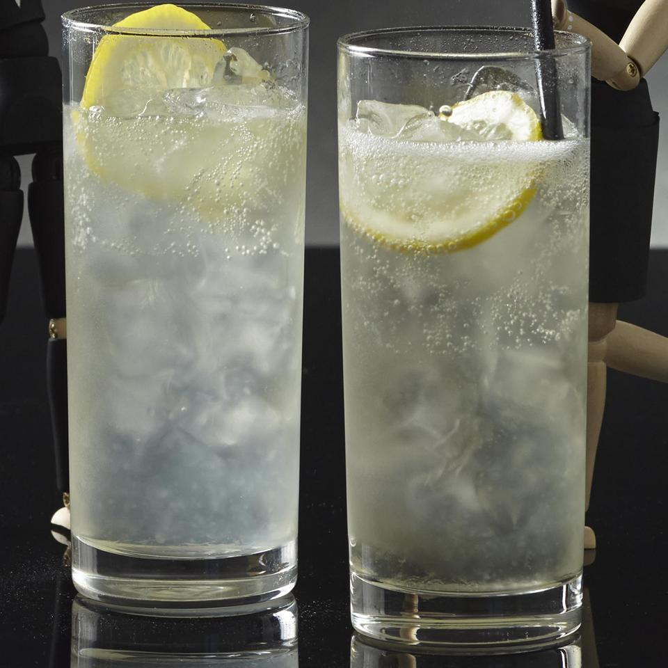 two cocktails in highball glasses with lemon wedges