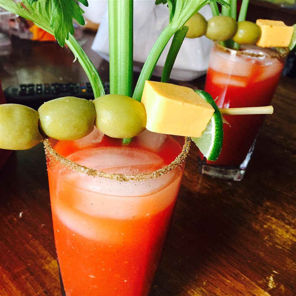 bloody mary with celery, olives, lime wedge, and cheese cube