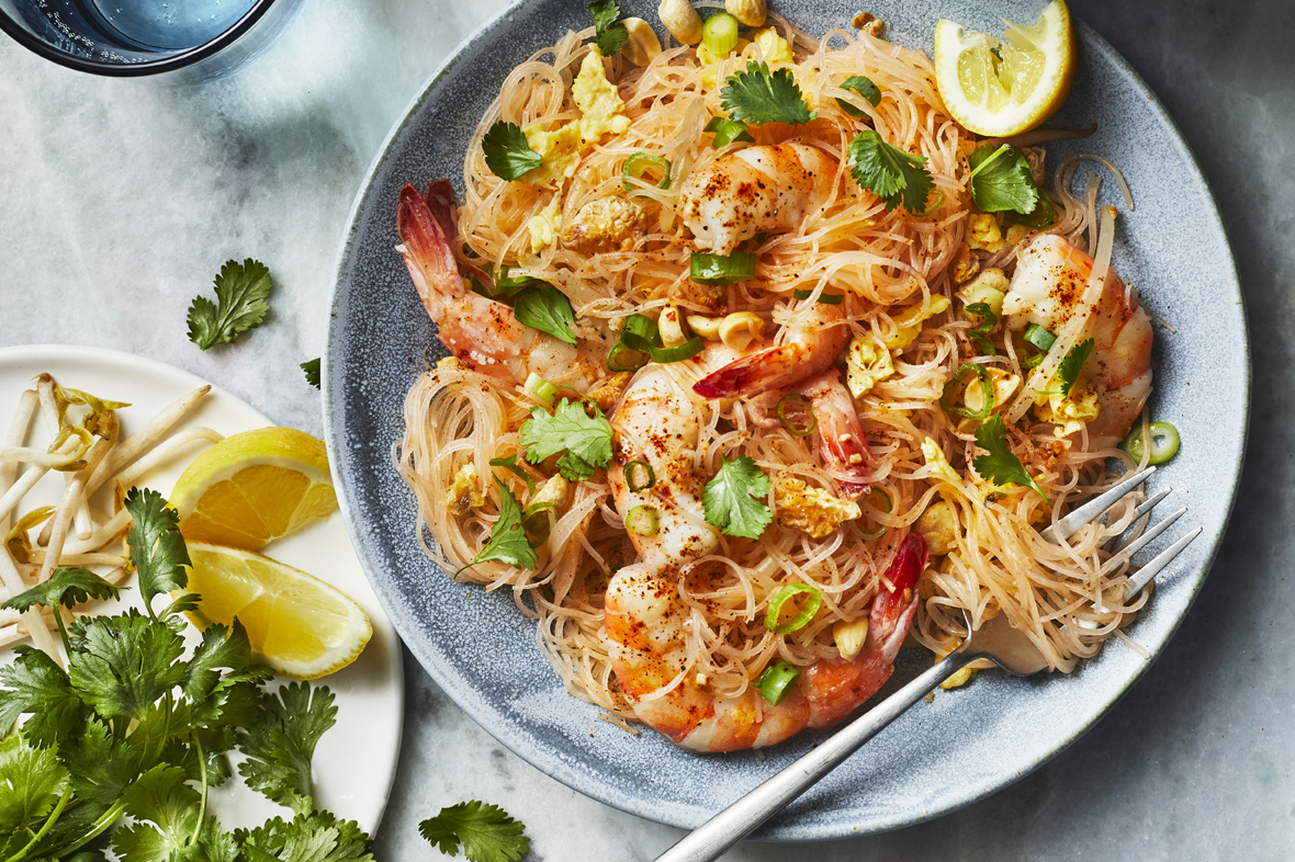A plate of shrimp fried noodles topped with cilantro, peanuts, and green onions
