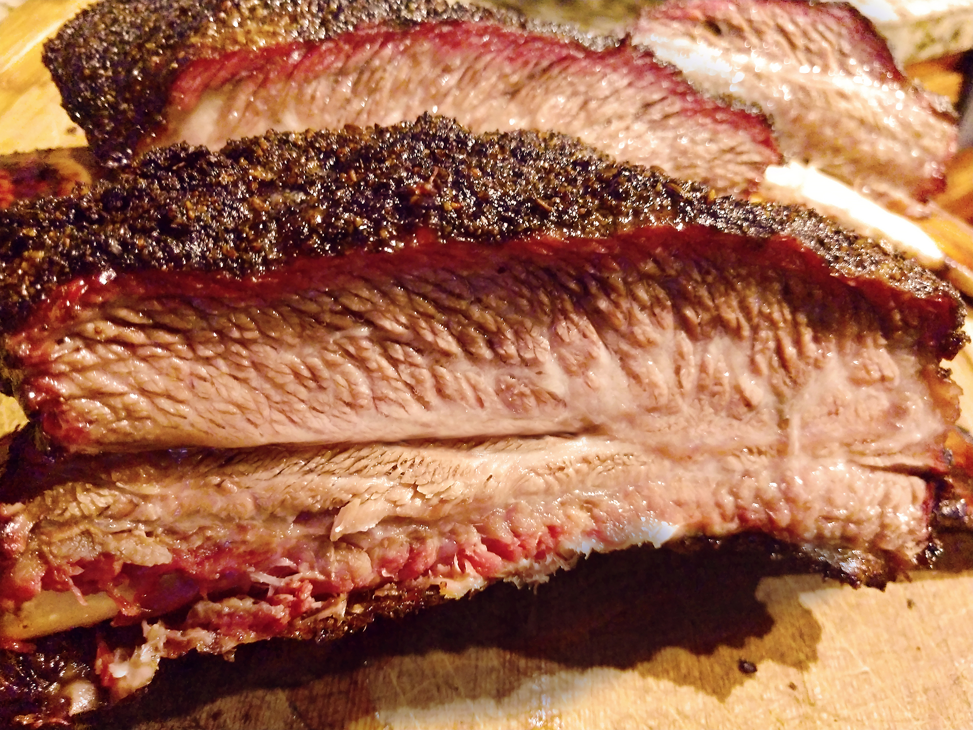 close up of texas barbeque beef ribs on a cutting board