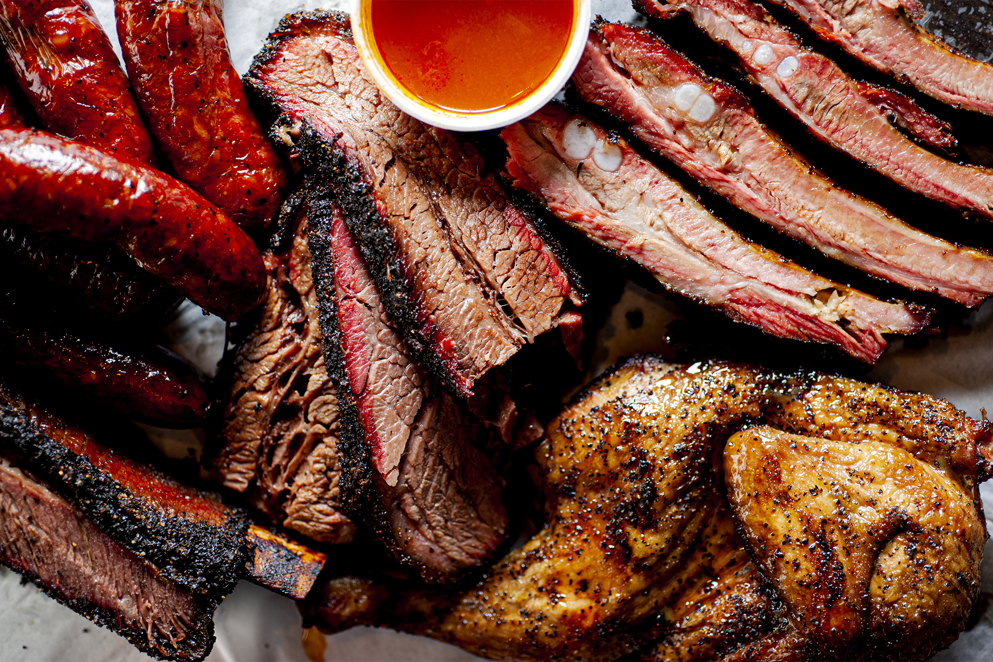 array of barbequed meats: ribs, sausages, brisket, and chicken