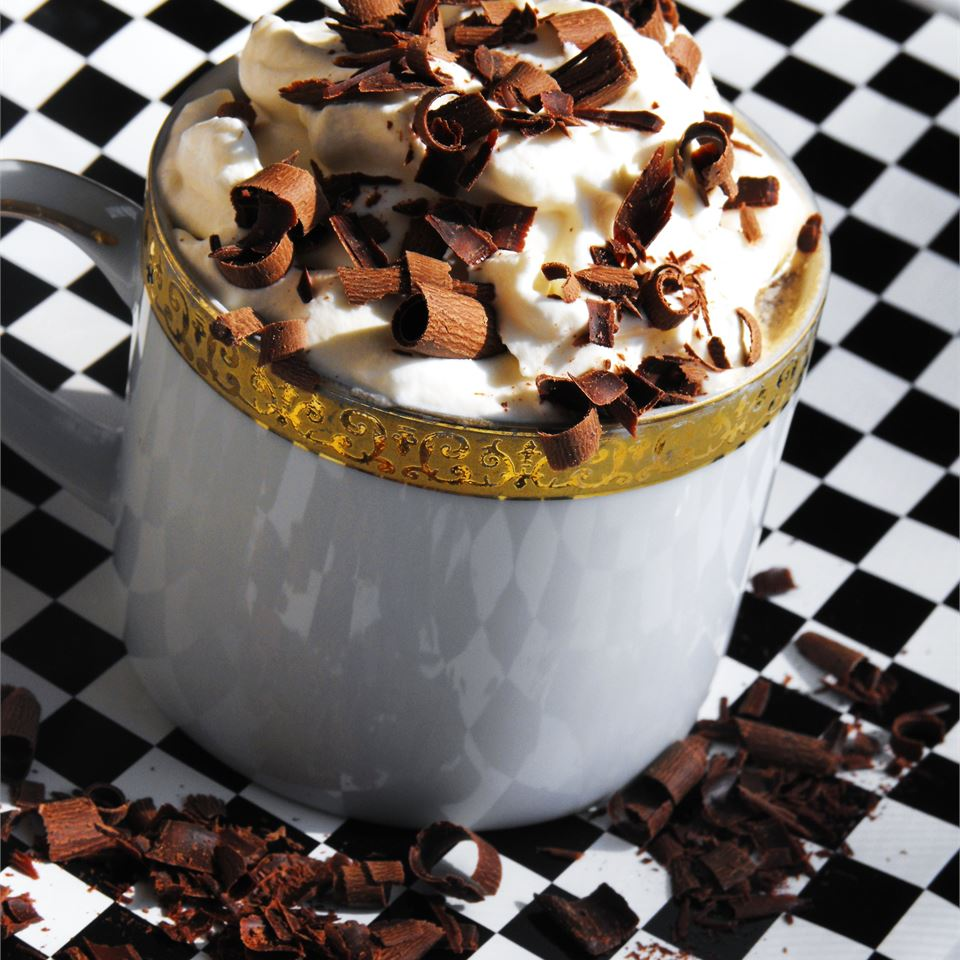 cafe latte milkshake topped with whipped cream and chocolate shavings