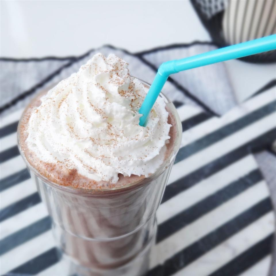 close up of a chocolate milkshake topped with whipped cream and cinnamon