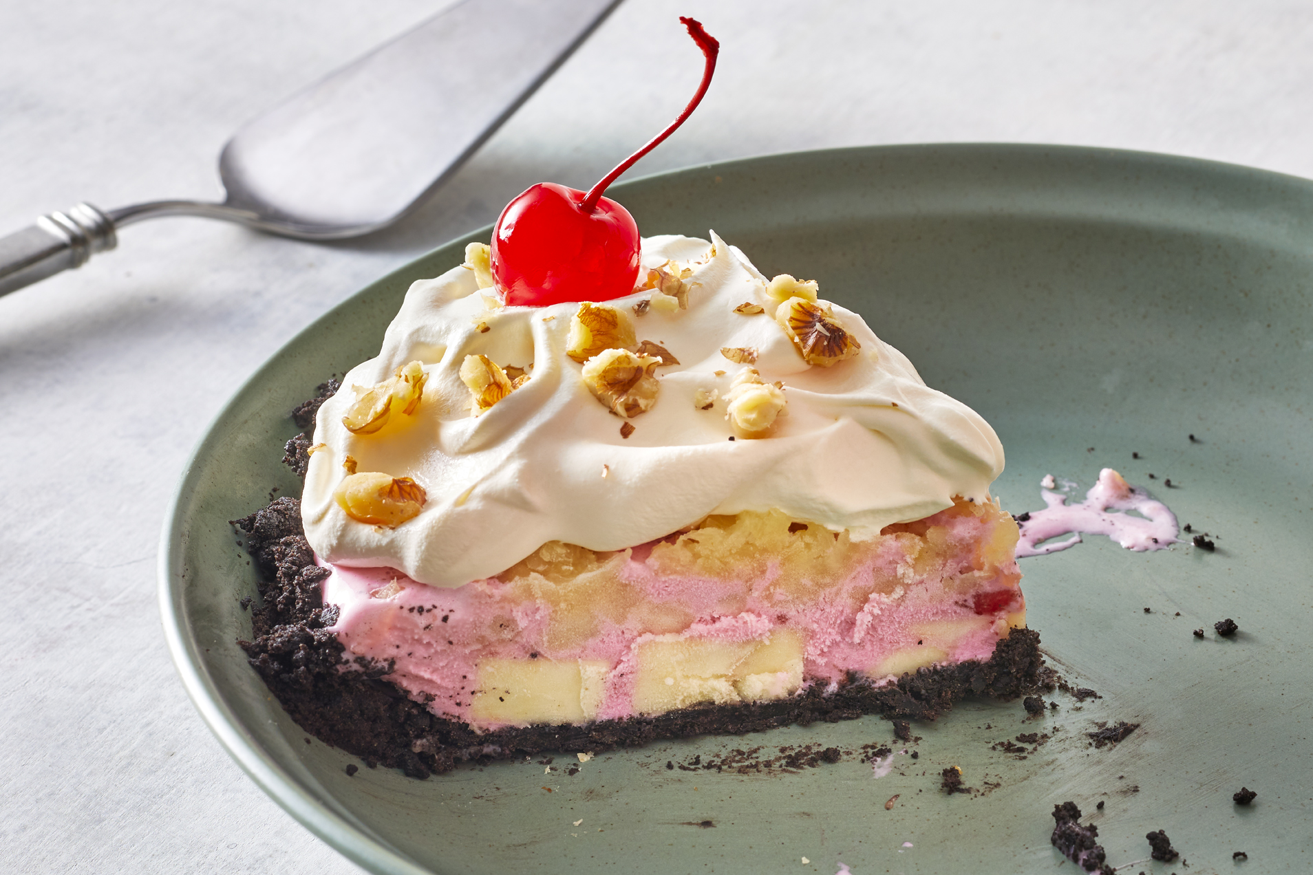 A single slice of banana split cream pie remains in an otherwise empty pie tin. Slice is topped with walnuts and a maraschino cherry
