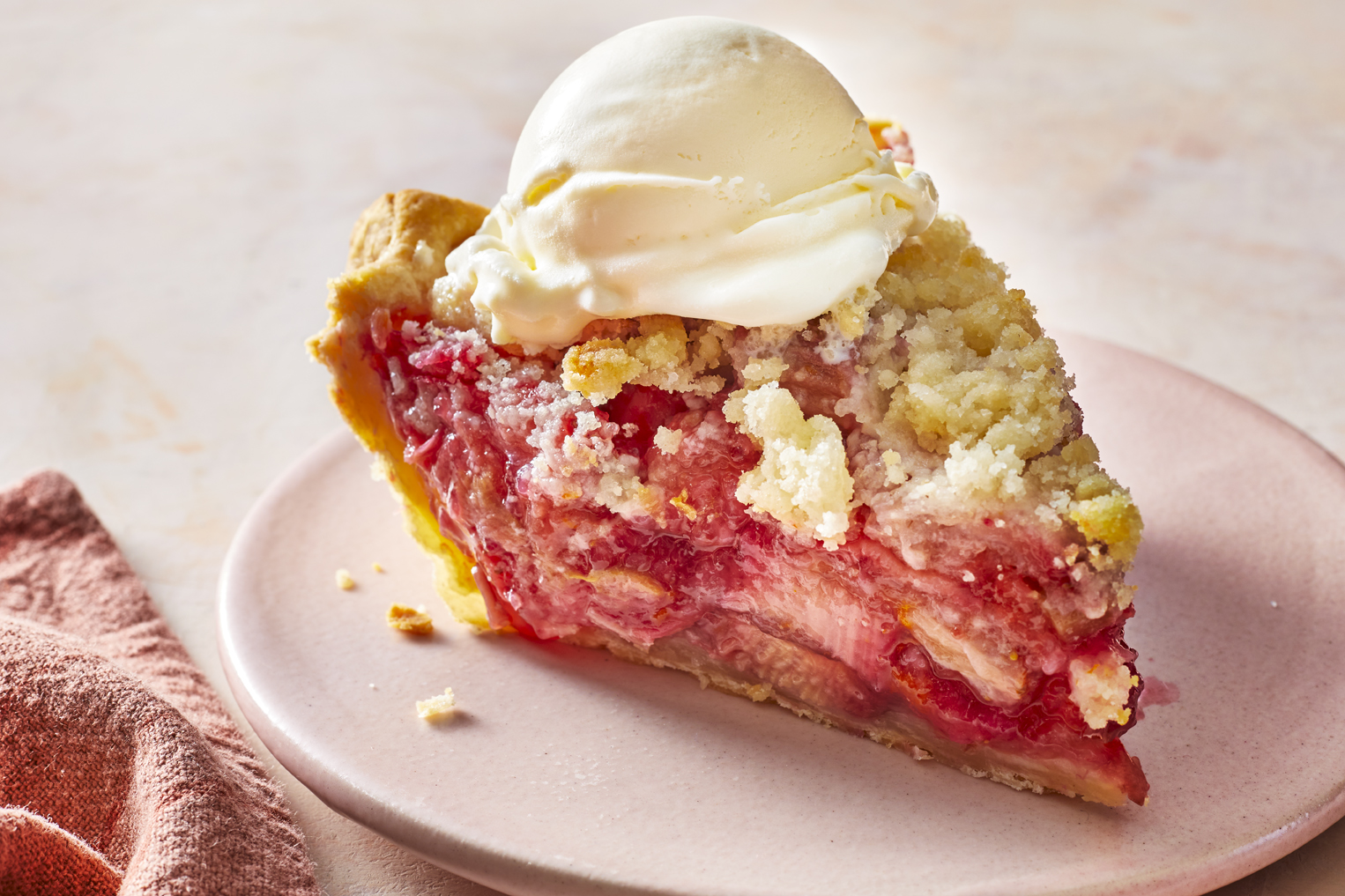 A single slice of strawberry rhubarb pie topped with a perfect scoop of vanilla ice cream