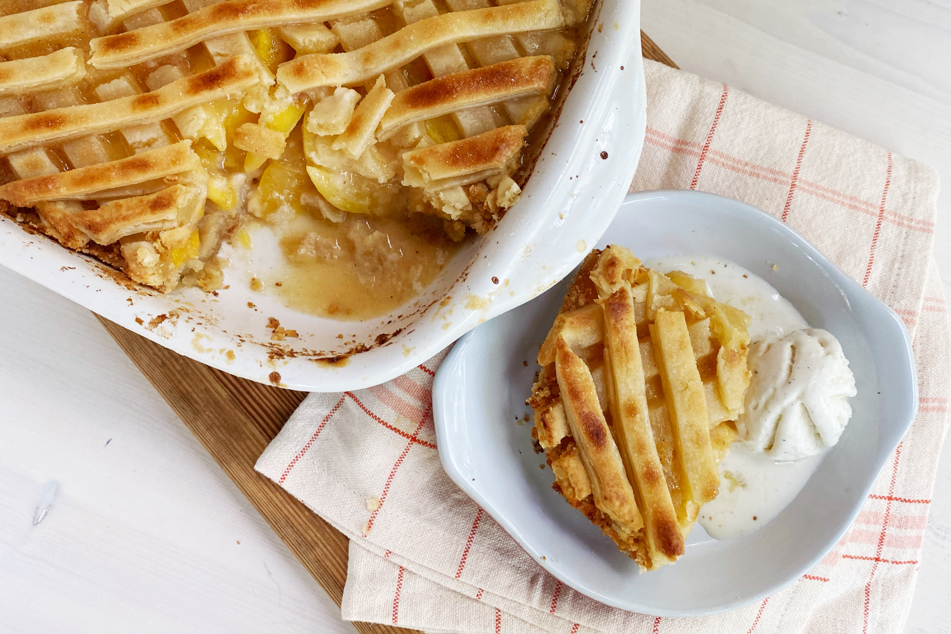 a white casserole dish containing a lattice topped peach cobbler sits cooling on a wooden board. A scoop has been taken out of the casserole dish and is plated with a half melted scoop of vanilla ice cream