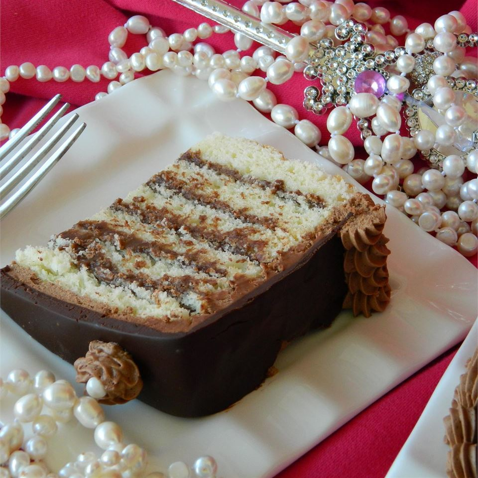 slice of layered cake with chocolate ganache on white plate with pearls