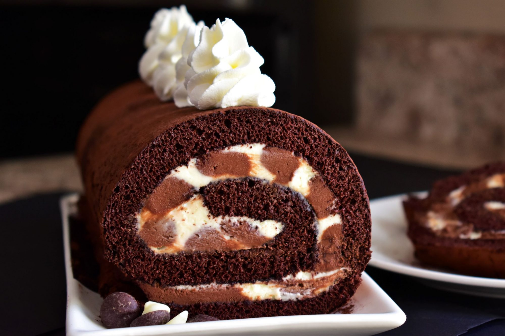 chocolate cake roll with chocolate and and white filling with whipped topping