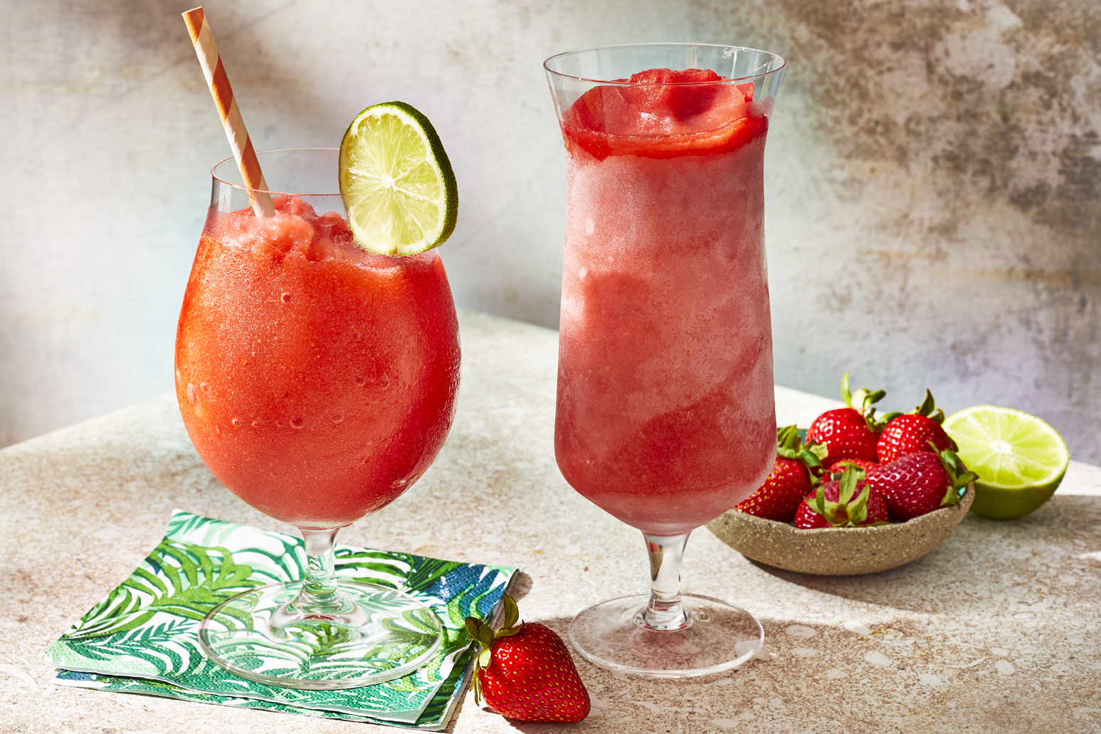 two frozen strawberry daiquiri drinks on table with a bowl of fresh strawberries and a tropical linen