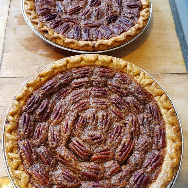 two whole pecan pies without corn syrup on a cutting board