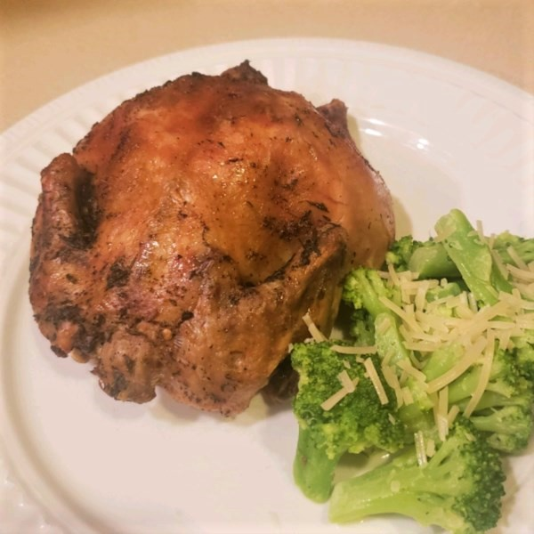 a cornish hen on a white dinner plate with a side of broccoli