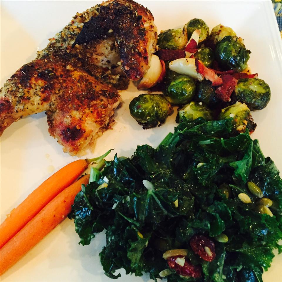the leg of a cornish hen with a side of vegetables on a white plate