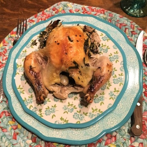 a roasted cornish hen on a blue floral dinner plate