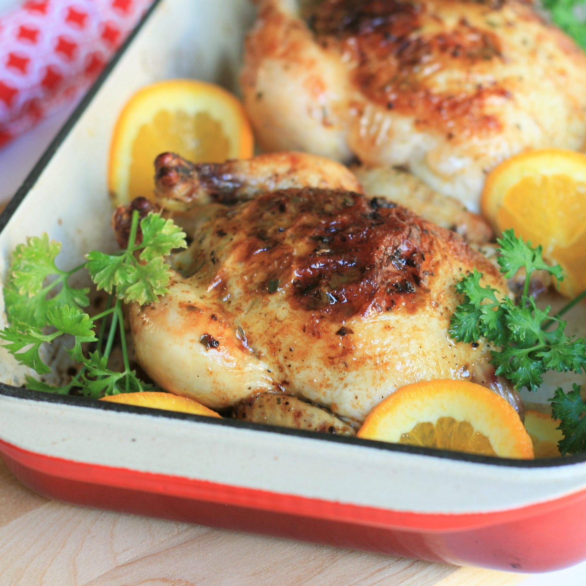 a red roasting pan with roasted cornish hens