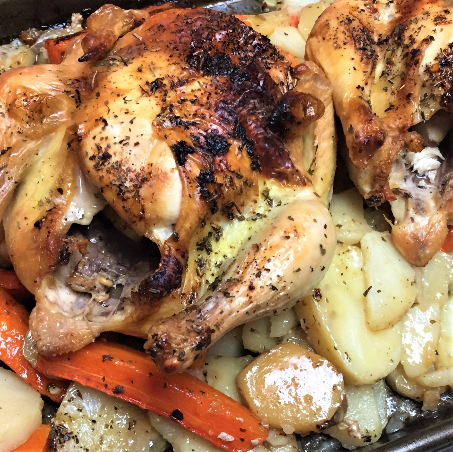 two cornish hens cooked in a sheet pan with vegetables