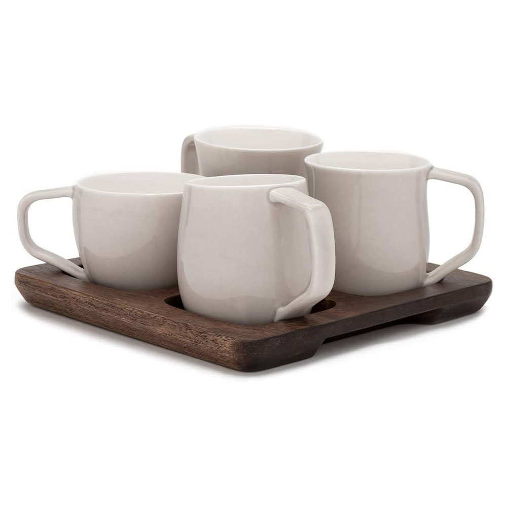 set of four white mugs on wooden board