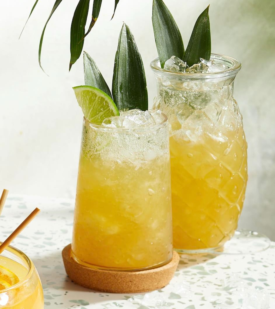 two glasses of Perky Pineapple Sipper tropical cocktails garnishes with lime slices and pineapple leaves