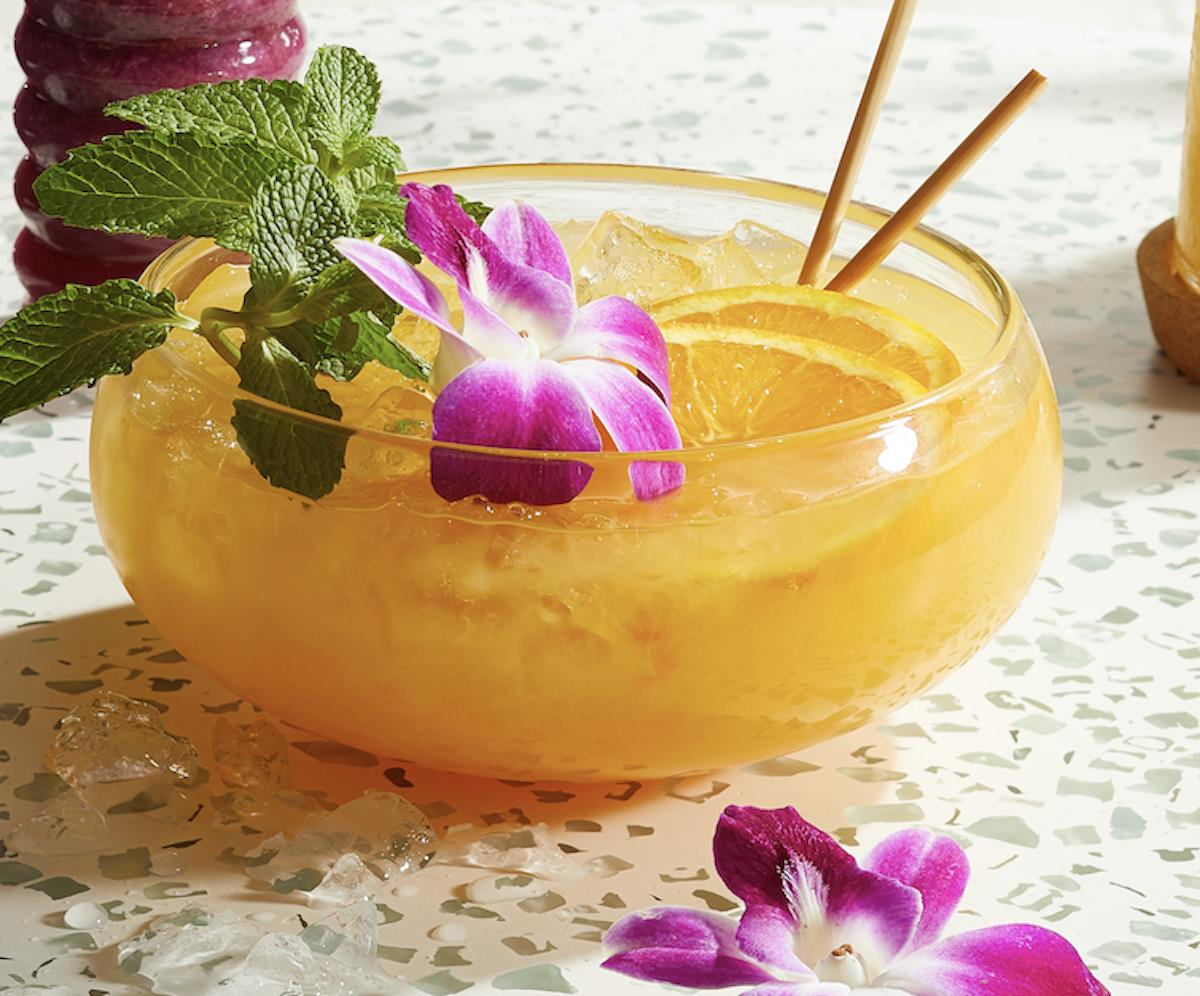 bowl of Lightened Up Scorpion Cup tropical cocktail garnished with mint leaves and orchid flowers