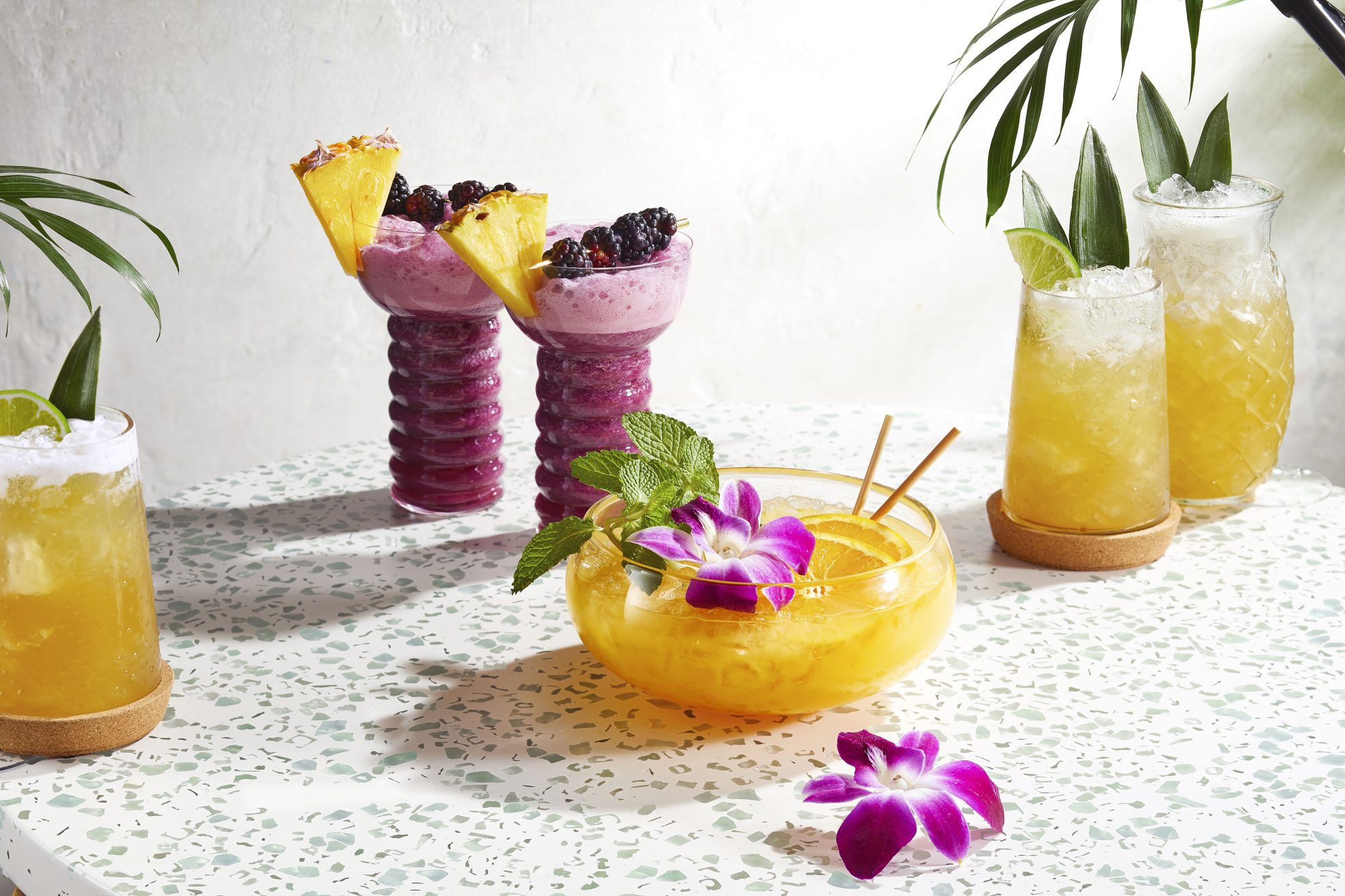 array of tropical drinks garnished with herbs, fruits, and flowers