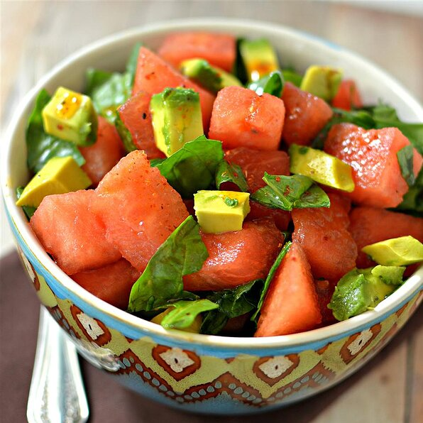 a bowl of cubed watermelon, diced avocado, and torn baby spinach leaves
