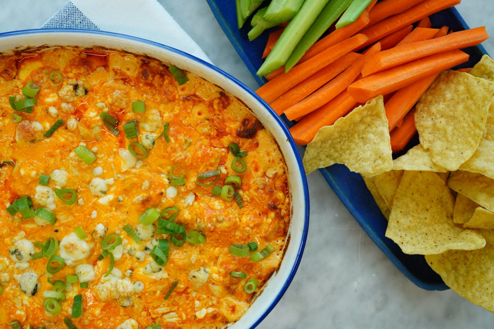 baking dish filled with The Best Buffalo Chicken Dip recipe garnished with blue cheese and minced scallions and served with celery sticks, carrot sticks, and tortilla chips